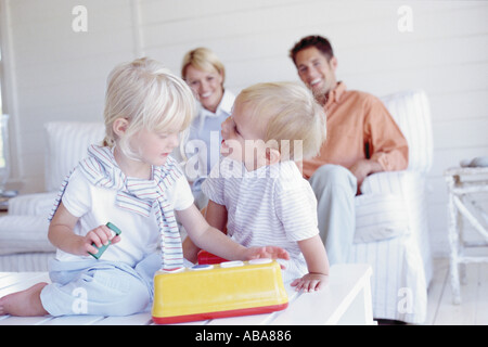 Kids playing with proud parents in the background - Stock Photo