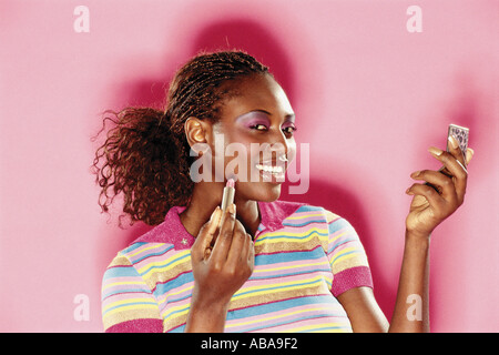 Woman putting make-up on - Stock Photo