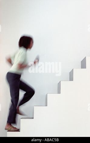 Woman running upstairs - Stock Photo