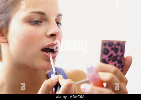 Teenage girl applying makeup - Stock Photo