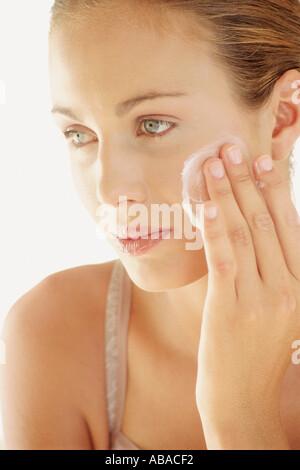 Woman applying face mask - Stock Photo