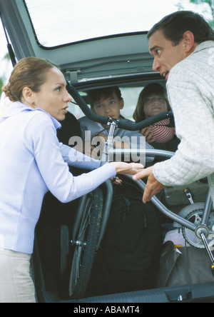 Parents putting bike into car trunk and arguing while children watch from car - Stock Photo