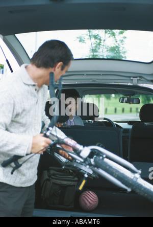 Man putting bike into car trunk - Stock Photo