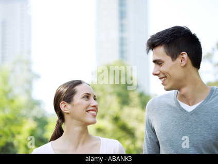 Young couple smiling at each other - Stock Photo