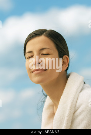Woman wearing bathrobe, smiling with eyes closed, sky in background - Stock Photo