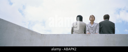 Woman standing between two men with backs turned - Stock Photo