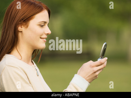 Young woman looking at cell phone, side view - Stock Photo