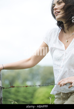 Woman next to fence - Stock Photo