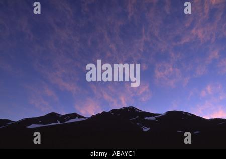 Light clouds catch the Sun's last rays over Cerro Pissis  in the Puna de Atacama, Argentina. - Stock Photo