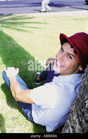 Man leaning against tree - Stock Photo