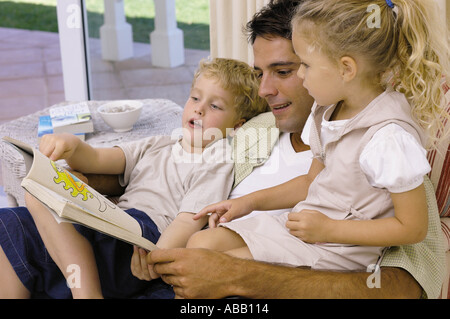 Father and kids looking at picture book - Stock Photo
