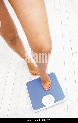 Woman Stepping On Weight Scale With Dumbbells And Tape