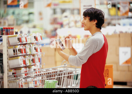 Man in using a handheld computer in shop - Stock Photo