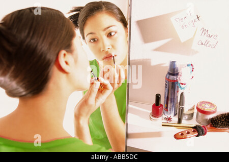 Teenage girl applying lipgloss - Stock Photo