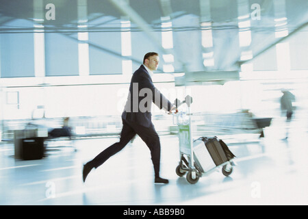 Businessman rushing in airport terminal - Stock Photo