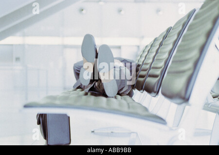Businessman relaxing in airport lounge - Stock Photo