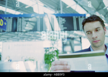 Businessman checking airline ticket - Stock Photo