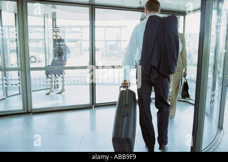 Businessman in airport terminal - Stock Photo