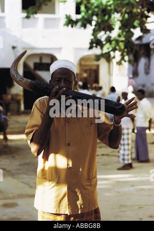 Man playing traditional SIWA or side blown horn Market place Lamu Island Kenya Coast East Africa - Stock Photo