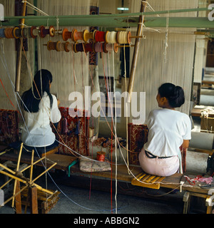Silk Carpet Factory with two women working skillfully at looms with their backs to the camera in Shanghai China