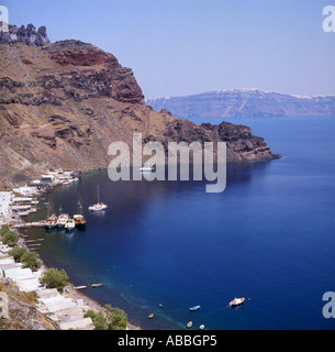 Cliff top view of Manolas harbour and bay with boats moored on jetty on Thirasia Island off Santorini The Greek - Stock Photo