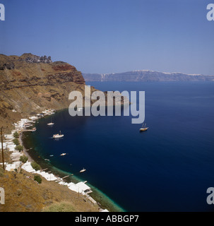 Cliff top idyllic sunny view of Manolas harbour & bay with boats moored on jetty on Thirasia Island off Santorini - Stock Photo