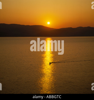 Golden sunset over Argostoli Bay with ripples and wake of boat in reflections on Cephalonia Island The Greek Islands - Stock Photo