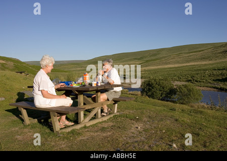 Couple picnicking at wooden table near river in Elan Valley Mid Wales - Stock Photo