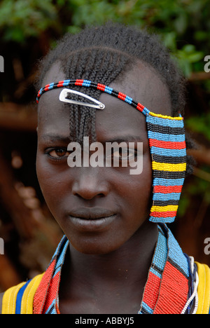 Portrait young beautiful girl wearing colourful head decoration on the market of Keyafer Ethiopia - Stock Photo