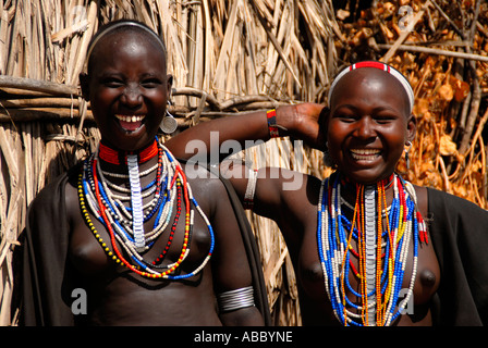 Two young laughing girls of the Arbore people wearing many colourful necklaces in front of a hut Ethiopia - Stock Photo