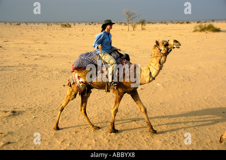 Camel trekking young woman wearing a hat is riding a camel in sand in wide open Thar desert near Jaisalmer Rajasthan - Stock Photo