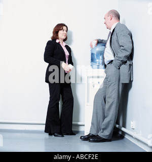 Two work colleagues talking by a water filter. - Stock Photo