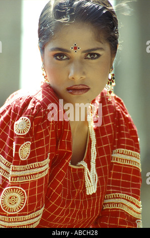 SSA70198 Young woman Shruti wearing pearl necklace red lipstick looking to the camera - Stock Photo