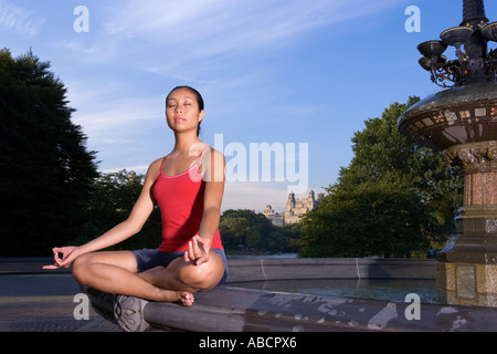 Woman meditating by fountain - Stock Photo