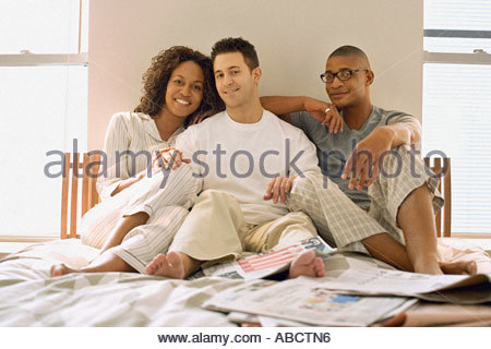 Woman and two men sitting on bed - Stock Photo