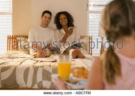 Girl bringing parents breakfast in bed - Stock Photo