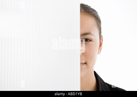 Businesswoman hiding behind a partition - Stock Photo