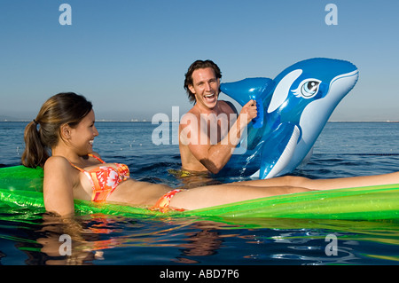 Couple in the sea with inflatables - Stock Photo