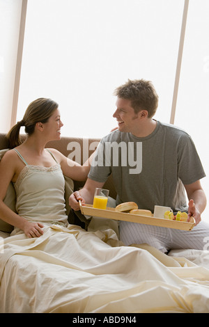 Man bringing woman breakfast in bed - Stock Photo