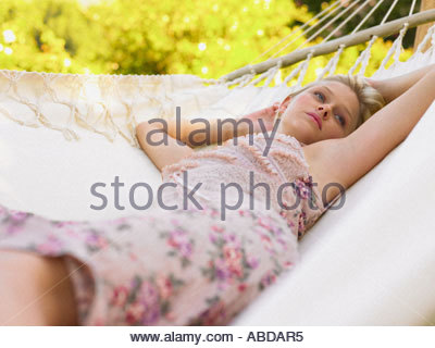 Young adult woman lying on a hammock - Stock Photo