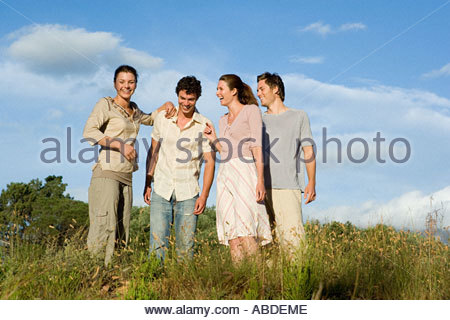 Friends standing in a field - Stock Photo