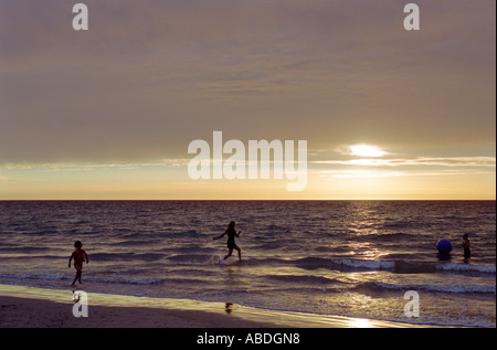 Three children playing on beach with ball near sunset - Stock Photo