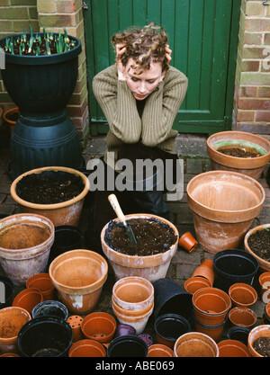Gardener looking at plant pots - Stock Photo
