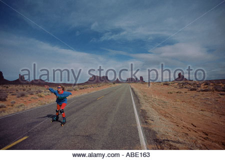 A roller skater on a deserted road - Stock Photo