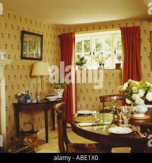 Antique Table Set For Lunch In Cottage Dining Room With Cream Patterned Wallpaper And Small Window