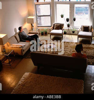 Couple sitting apart in living room - Stock Photo