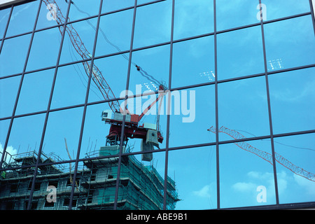 Reflection of construction crane on glass - Stock Photo