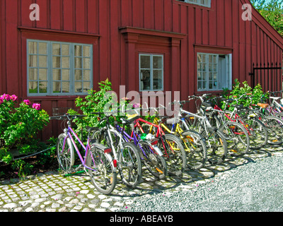 Trondheim parked parking bicycles bikes in front of an red old timber house woodhouse in a lane in the old town - Stock Photo