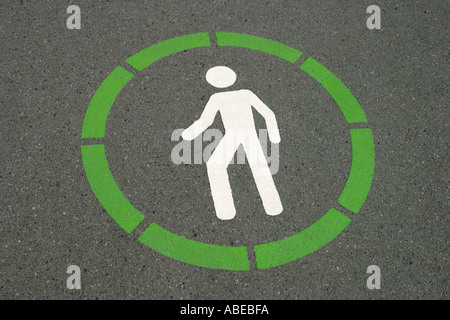 A green and white sign painted on the road or pavement indicating a pedestrian crossing or walking path  - Stock Photo