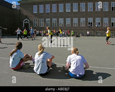 young people teenies about 13 to 17 years old making sport on schoolyard in summer three girls sitting on ground - Stock Photo